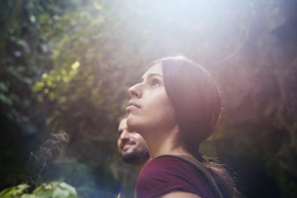 Female hiker with boyfriend in a forest looking up