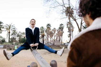 Exuberant couple on a seesaw at a playground