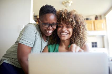 Laughing women hugging and using laptop