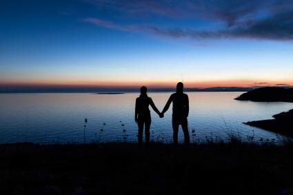 Silhouette of couple holding hands at sunset