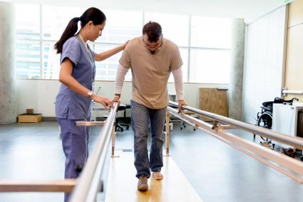 Patient takes his first steps using the orthopaedic parallel bars under the guidance of the physical therapist