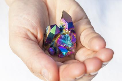 Piece of Rainbow Titanium Aura Crystal in hands