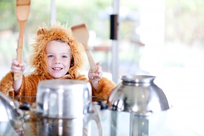 Boy dressed as a lion pretending to be drummer
