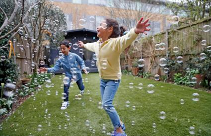kids chasing bubbles with arms out