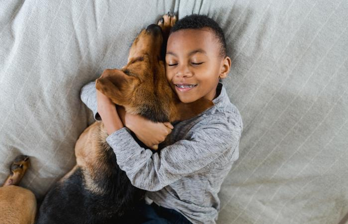 Boy hugging adopted dog