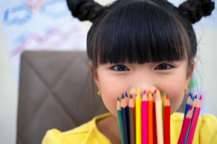 Cute little girl holding colorful felt pens