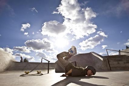 Boy having fallen off skateboard in park