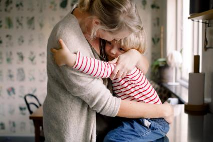 Loving daughter embracing mother while sitting on kitchen counter