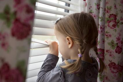 Child indoors peering out through window blinds