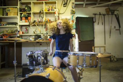 Teenage girl drumming in garage