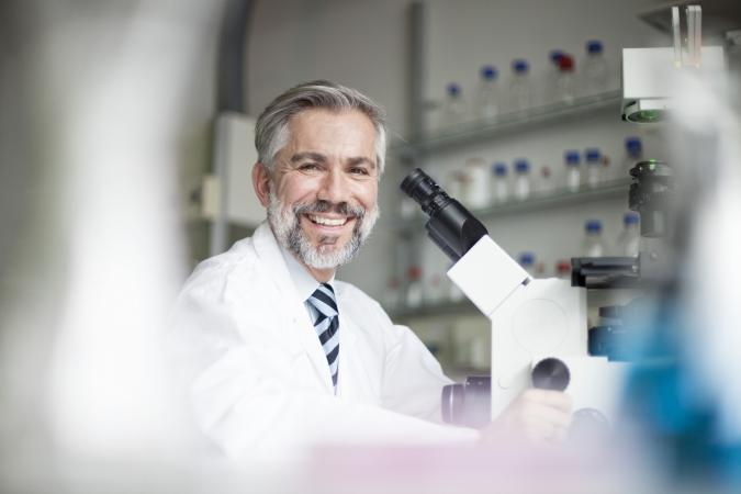 Smiling scientist in laboratory with microscope