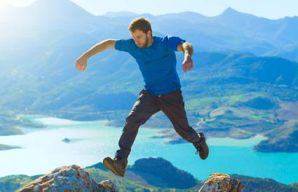 man jumping at the top of a mountain