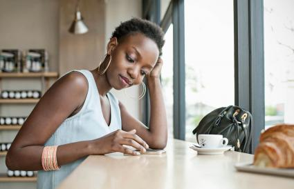 woman in cafe with mobile phone