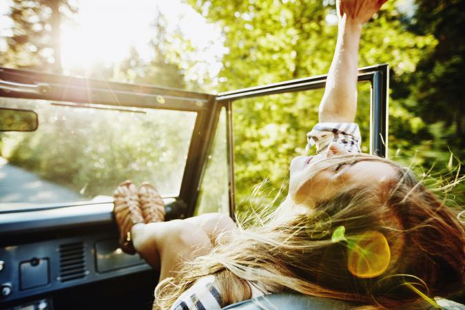 Woman riding in passenger seat of convertible