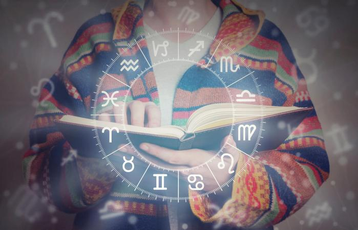 person with book and horoscope wheel