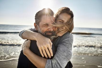 Carefree mature man and woman hugging at the sea