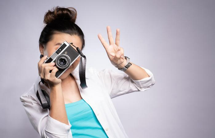 Woman gesturing while photographing