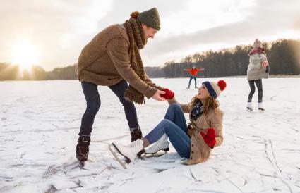 man helping ice skating woman