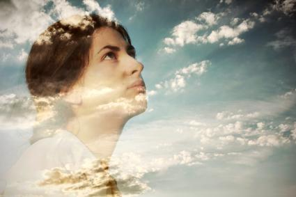 Pensive young woman and cloudy sky