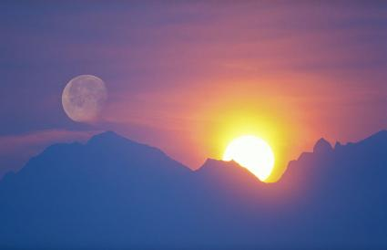 sun and moon behind mountain