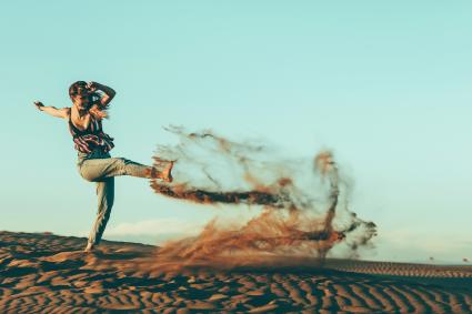 Young woman kicking sand in desert landscape