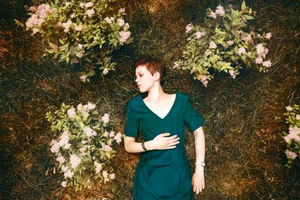 Woman laying in grass near flowers