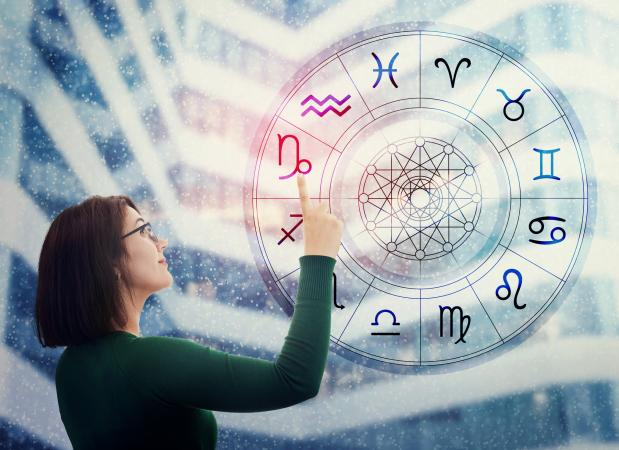 Woman choosing a zodiac sign from the astrological wheel
