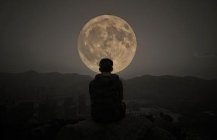 Man Sitting Against Moon