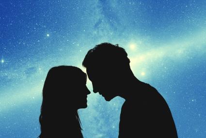 Siluetas de una pareja de jóvenes bajo el cielo estrellado