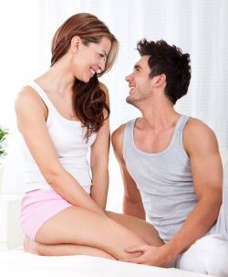 sonriente joven pareja sentada en la cama