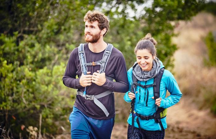Sonriente pareja haciendo excursionismo