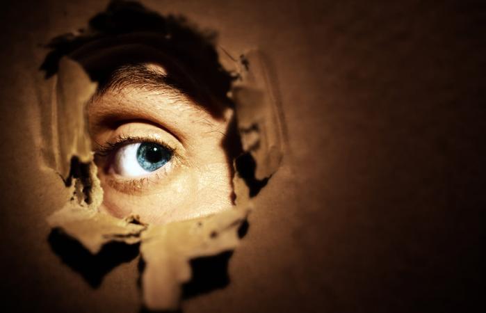 Ojo espiando a través de un agujero