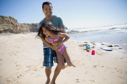 Papá jugando con su hija en la playa