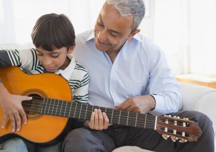 Abuelo mirando a su nieto tocar la guitarra