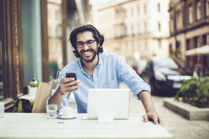 Hombre sonriendo y sosteniendo telefono