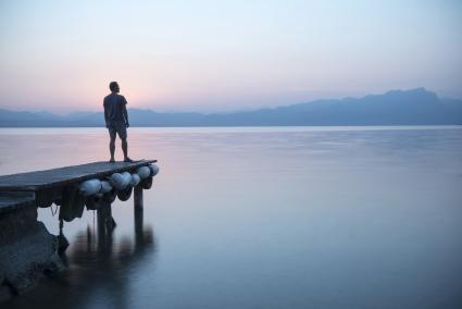 Hombre en un puente mirando al lago