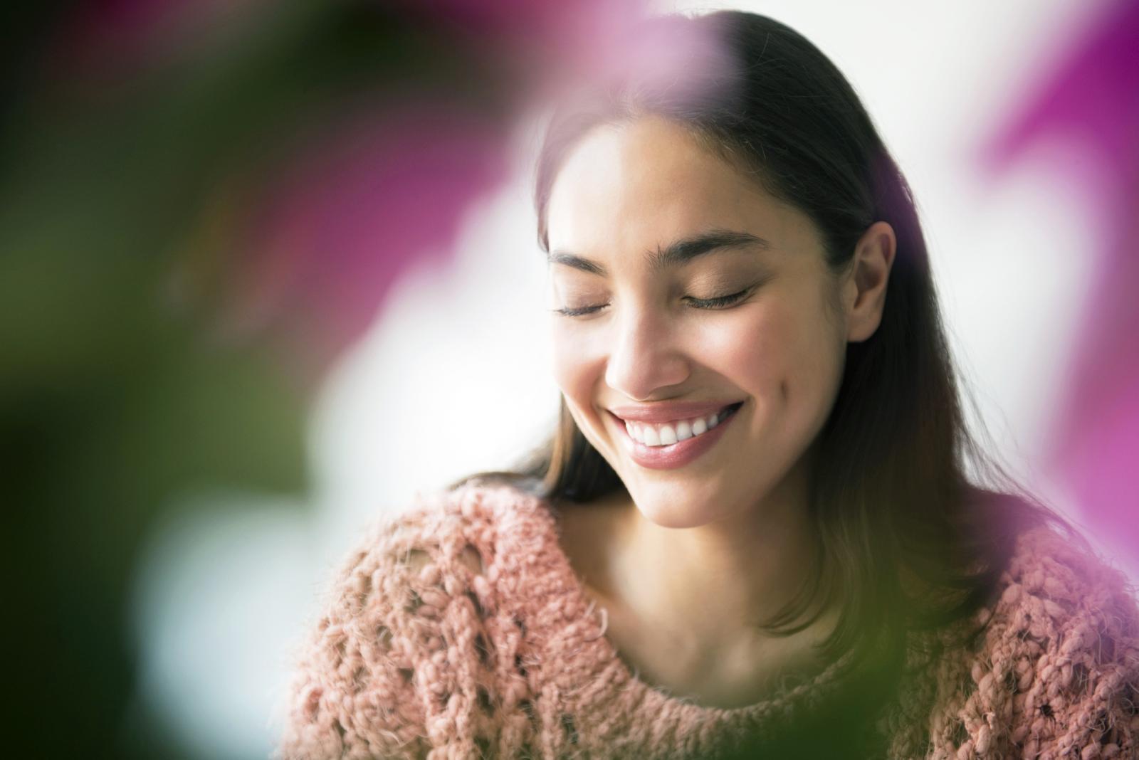 Mujer coqueta detras de flores rosas
