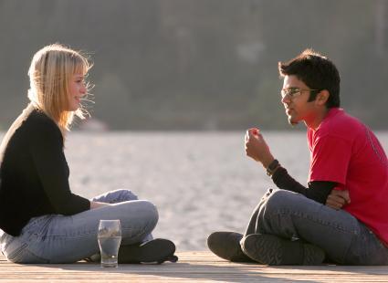 Pareja hablando sentada al lado de un lago
