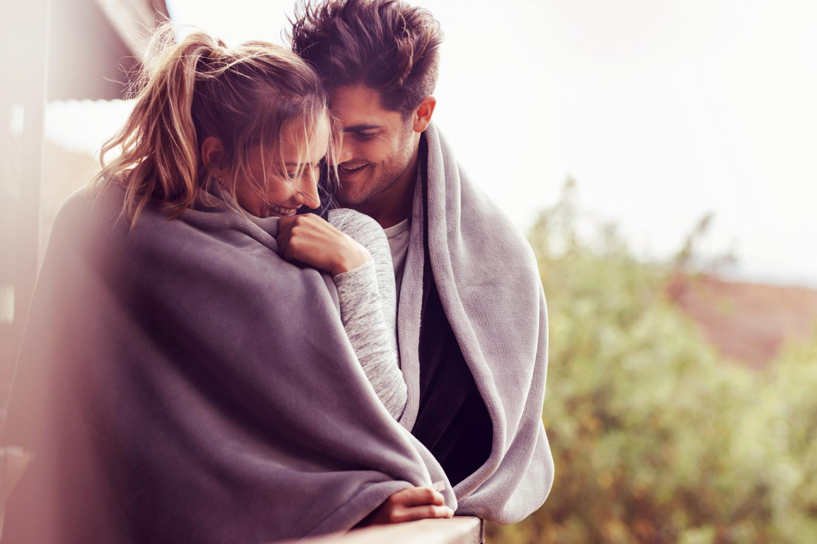 Man and woman standing together in a balcony wrapped in a blanket embracing and smiling