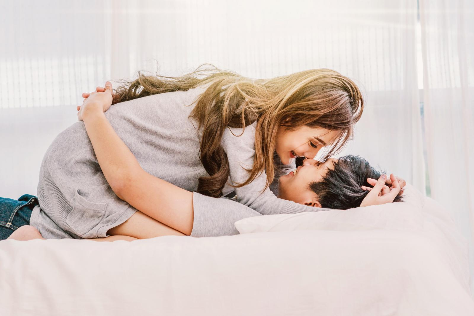 Pareja besandose en la cama