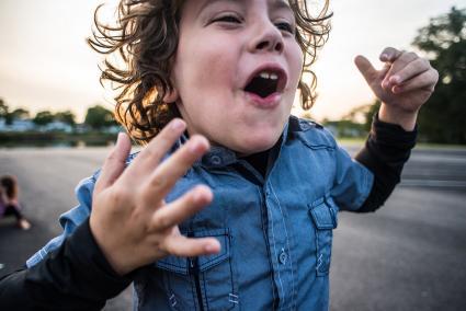 feliz niño géminis con pelo rizado