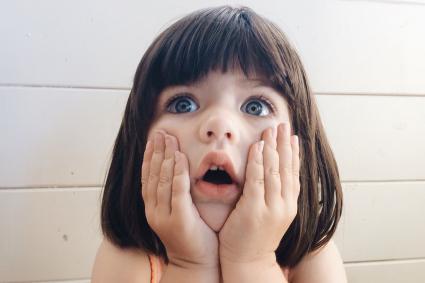 niño libra sosteniendo su cara