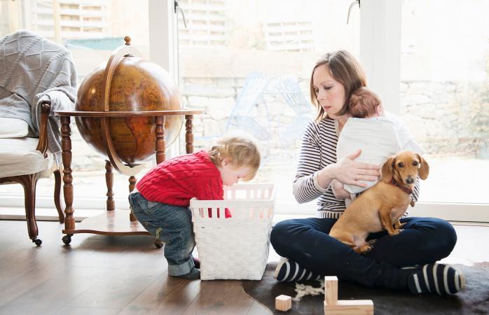 Niño jugando en casa con su madre y su hermanita