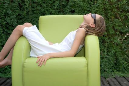 Niña durmiendo la siesta en un sillón al aire libre