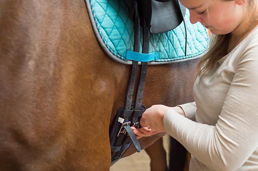 Woman Locking Horse Saddle