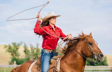 Cowgirl throwing lasso on horseback