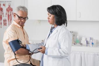 doctor checking seniors blood pressure