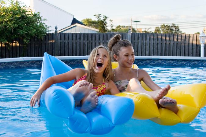 Kids on inflatables in swimming pool