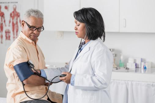 doctor checking seniors blood pressure