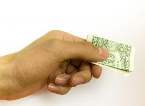 Image of hand offering folded dollar bill